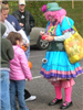 Clown preparing balloon animal for child