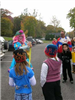 Group of children watching clown prepare balloon animals