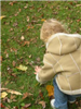 Child in brown jacket picking up a piece of candy