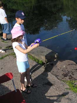 Boy watches as girl fishes