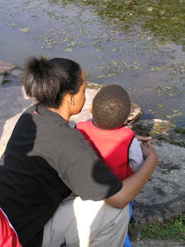 Mom holding son at waters edge helping him fish (PDF)