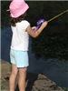 Child casts her reel while fishing