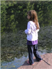 Young girl looks out over pond
