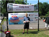 Boy holding tackle box in front of Fishing Derby sign