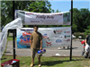 Boy in brown shirt holding tackle box in front of Fishing Derby sign