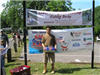 Boy in brown shirt in front of Fishing Derby sign