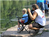 Boy sitting in chair fishing and parent watching boy fish (PDF)